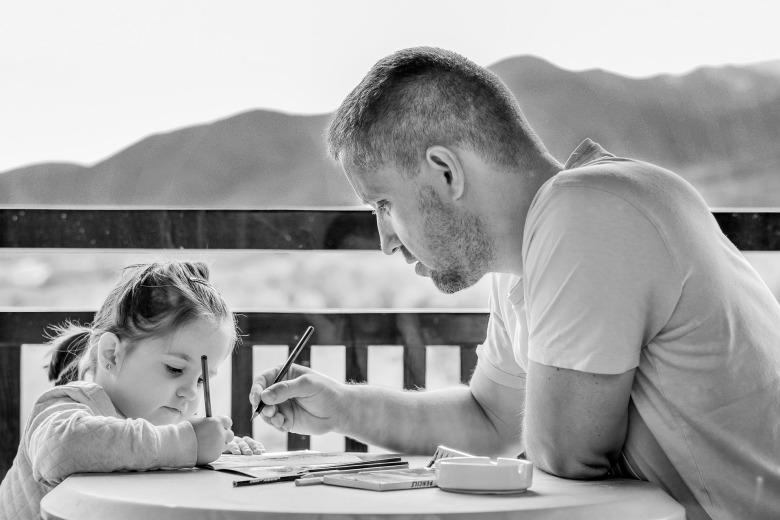 un padre pintando con su hija