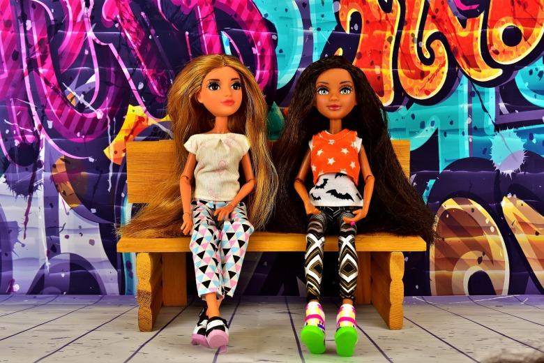 dos muñecas en un banco