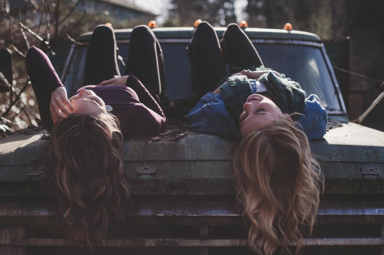 Dos amigas conversan recostadas sobre el capot de una camioneta