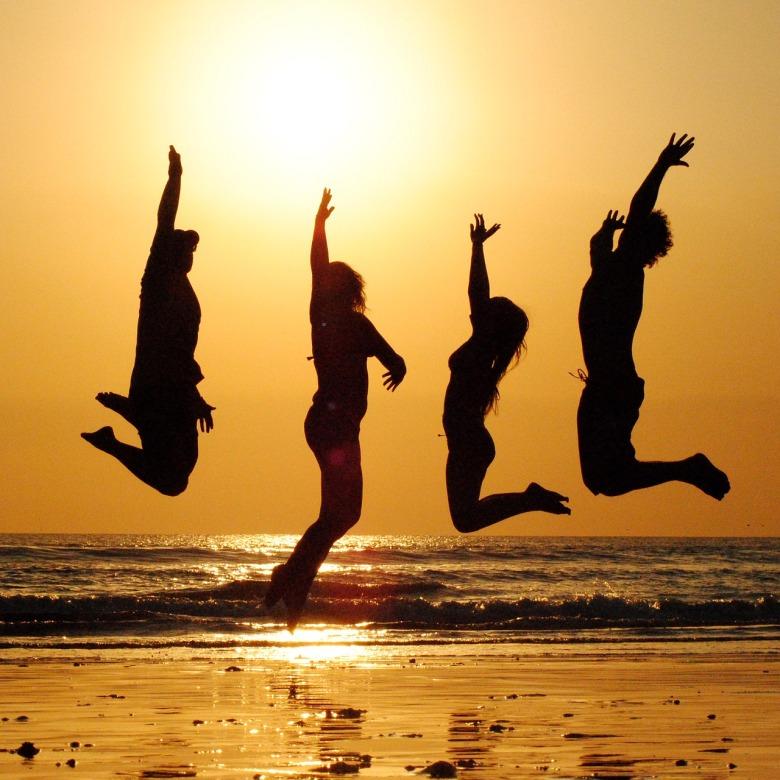 Cuatro amigos saltan en la playa al atardecer