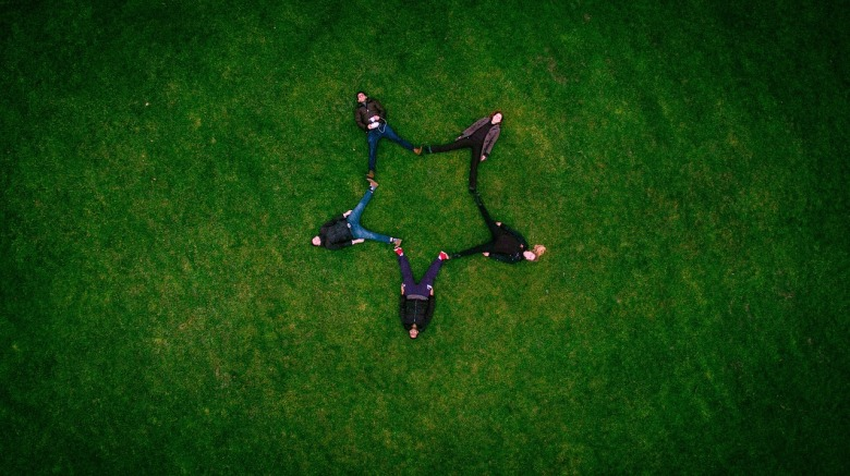 Cinco amigos acostados en el césped forman una estrella con sus piernas