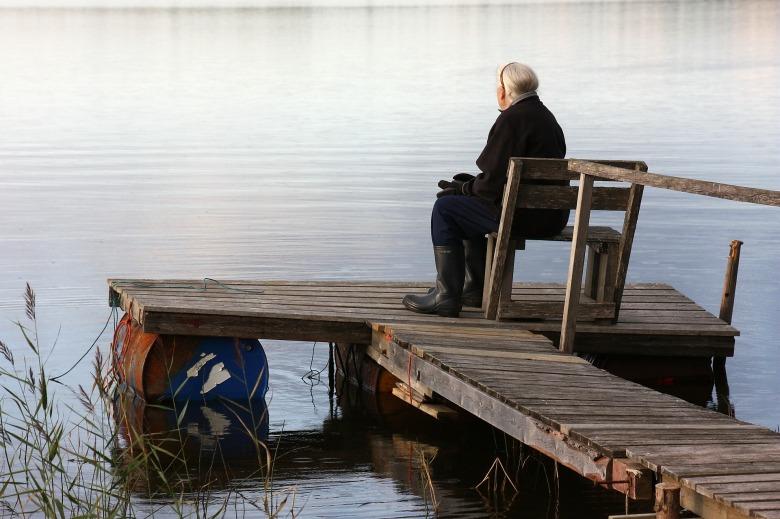 mujer sentada en un muelle contemplando el lago