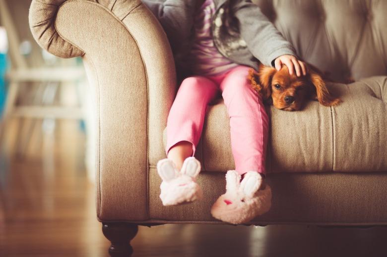 Una niña en pantuflas con su cachorro, sentada en el sillón