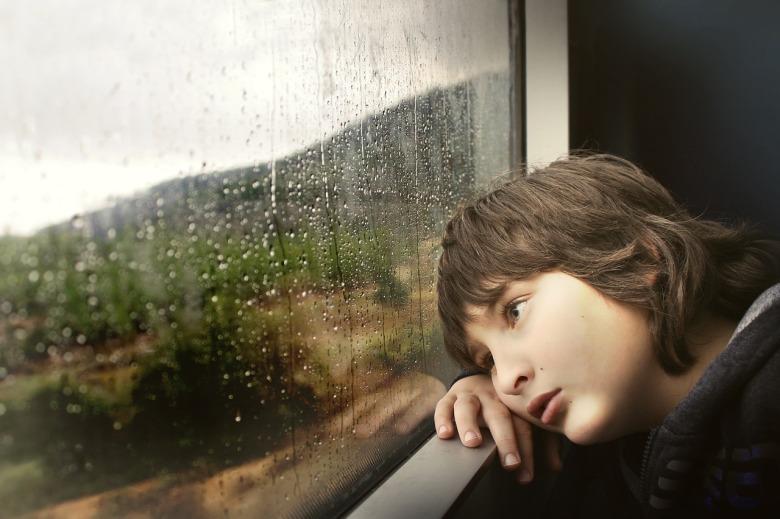Un niño mira la lluvia por la ventana con cara de aburrido