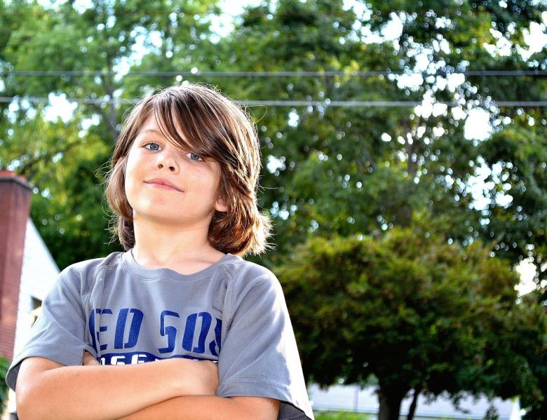 Un niño que juega al aire libre posa de brazos cruzados