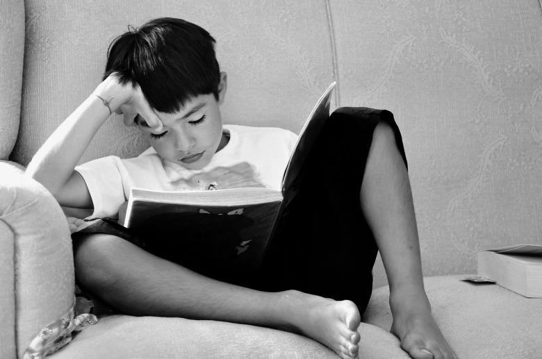 Un niño lee un libro sentado en un sillón