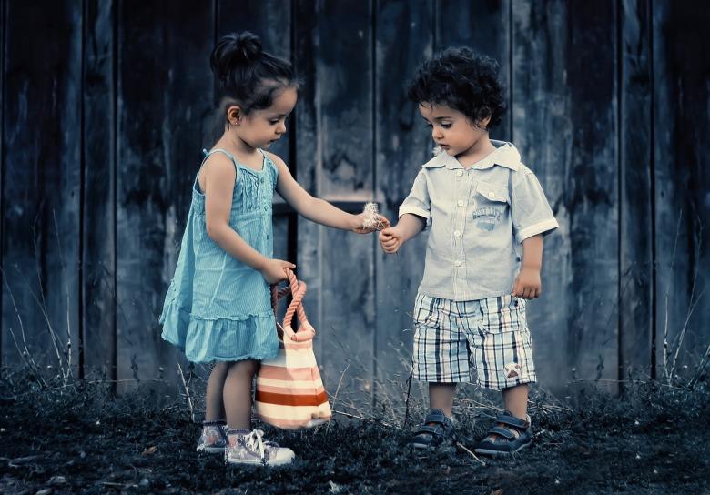 Un niño y una niña intercambian un juguete en un jardín