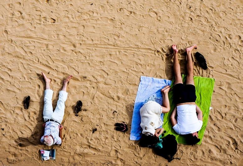 pareja descansa en la arena y un hombre mayor reflexiona