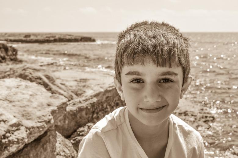un niño sonríe delante del mar
