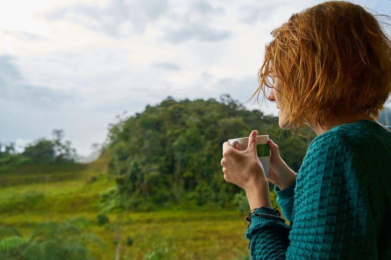 Una chica toma un café en un campo