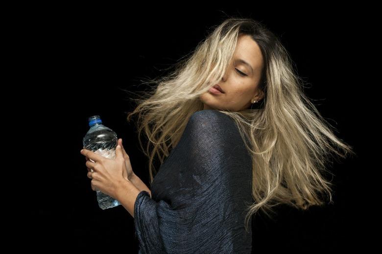 Una chica toma agua de una botella