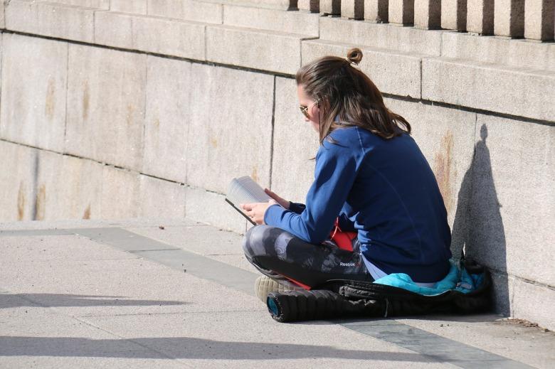 una mujer lee un libro al sol
