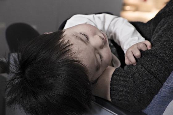 un bebe duerme en los brazos de su mamá