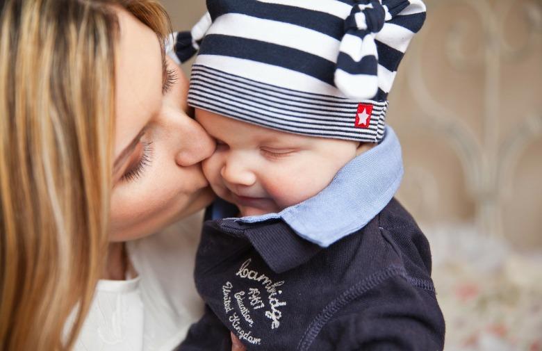 una mamá besa a su bebe